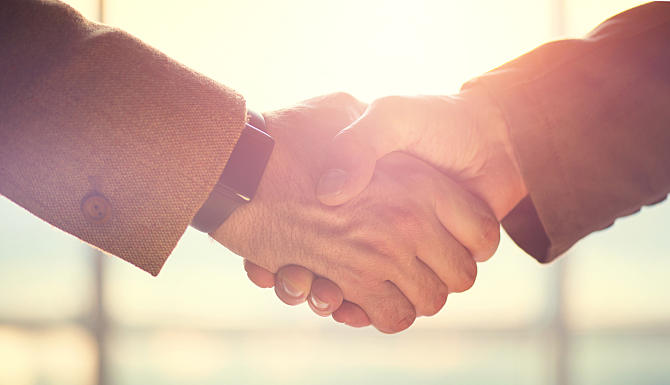 Business handshake. Business handshake and business people concept. Two men shaking hands over sunny